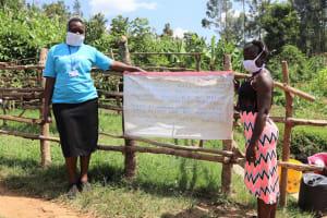 The Water Project: Emulakha Community, Nalianya Spring -  The Facilitators Karen And Jemimah Posing Next To The Chart