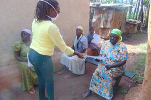 The Water Project: Shihungu Community, Shihungu Spring -  Distributing Training Manuals