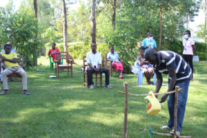 The Water Project: Emukangu Community, Okhaso Spring -  A Community Elder Leads A Handwashing Session