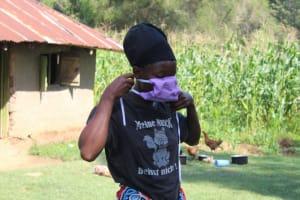 The Water Project: Emukangu Community, Okhaso Spring -  A Community Member Tries On Her New Mask