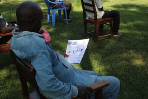 The Water Project: Emukangu Community, Okhaso Spring -  Using Handouts At The Trainings
