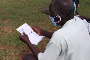 The Water Project: Kalenda A Community, Webo Simali Spring -  An Elder Follows Training Using A Handout