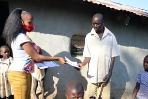 The Water Project: Sasala Community, Kasit Spring -  Distributing Handouts About Coronavirus