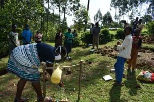 The Water Project: Bumavi Community, Shoso Mwoga Spring -  Using A Handwashing Station Set Up At The Community