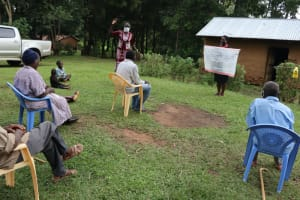 The Water Project: Murumba Community, Muyokani Spring -  Training With The Help Of The Reminder Chart