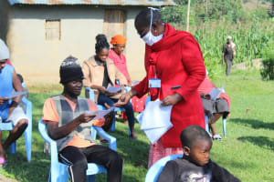 The Water Project: Shiamboko Community, Oluchinji Spring -  Trainer Kayi Issuing Covid Informational Pamphlets