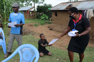 The Water Project: Mumuli Community, Shalolwa Spring -  Ms Betty Handing Out The Training Manuals