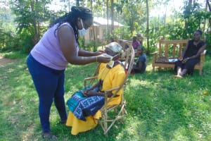 The Water Project: Mukhuyu Community, Shikhanga Spring -  Trying Mask On An Elderly Lady