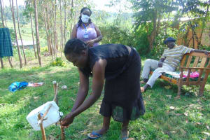The Water Project: Mukhuyu Community, Shikhanga Spring -  Using A Leaky Tin To Handwash