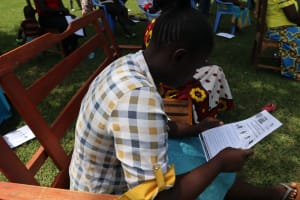 The Water Project: Ematiha Community, Ayubu Spring -  A Lady Going Through The Training Aid Document