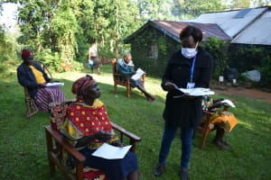The Water Project: Shitoto Community, Laurence Spring -  Facilitator Handing Out Covid Informational Pamphlets