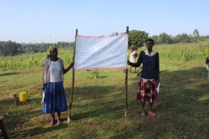 The Water Project: Emusanda Community, Walusia Spring -  Community Members Holding Up The Prevention Reminders Chart