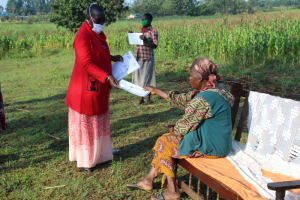 The Water Project: Emusanda Community, Walusia Spring -  Ms Kayi Issuing Informational Pamphlets On Covid