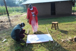 The Water Project: Emusanda Community, Walusia Spring -  Trainers Mounting The Chart To Support Poles