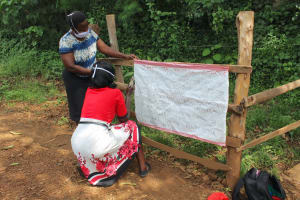 The Water Project: Harambee Community, Elijah Kwalanda Spring -  Staff Installing Covid Posters At The Spring