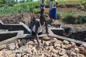The Water Project: Mukhuyu Community, Chisombe Spring -  Backfilling With Stones