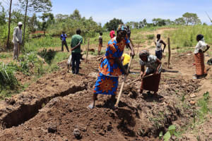 The Water Project: Mukhuyu Community, Chisombe Spring -  Community Members Levelling The Site