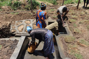 The Water Project: Mukhuyu Community, Chisombe Spring -  Site Maintenance Training Washing Of The Spring