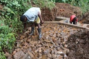 The Water Project: Harambee Community, Elijah Kwalanda Spring -  Stone Backfilling