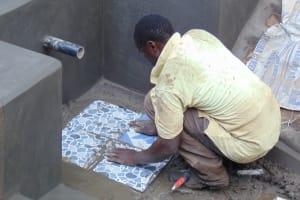 The Water Project: Harambee Community, Elijah Kwalanda Spring -  Tile Setting