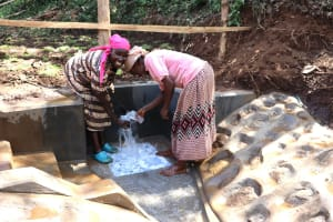 The Water Project: Harambee Community, Elijah Kwalanda Spring -  Community Members Feeling The Coldness Of Water