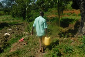 The Water Project: Mahola Community, Oyula Spring -  Taking Home Water From Oyula Spring