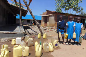 The Water Project: Ivakale Primary School & Community - Rain Tank 1 -  Pupils With Water Containers At Central Dropoff Point