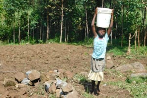 The Water Project: Mabanga Community, Ashuma Spring -  Taking Water Home From Ashuma Spring