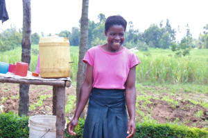The Water Project: Burachu B Community, Shitende Spring -  A Light Moment While Letting Her Hands Air Dry