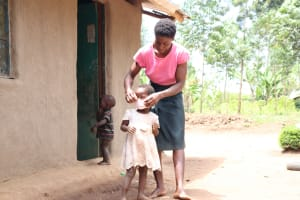 The Water Project: Burachu B Community, Shitende Spring -  Magdalene Helping Her Daughter Lilly Put On Her Mask