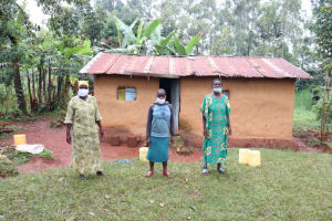 The Water Project: Mushina Community, Shikuku Spring -  Beatrice With Her Sister And Daughter In Front Of Their Home
