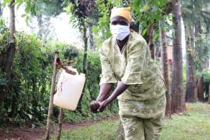The Water Project: Mushina Community, Shikuku Spring -  Beatrice Uses The Handwashing Station Outside Her Home