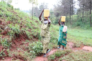 The Water Project: Mushina Community, Shikuku Spring -  Leaving The Spring With Water For Use