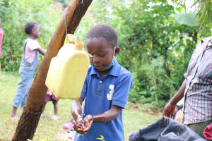 The Water Project: Hirumbi Community, Khalembi Spring -  Alices Son Baraka Washes His Hands