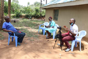 The Water Project: Buhayi Community, Nasichundukha Spring -  Jemmimah And Camera Operator Allan Conducting The Interview With Joseph