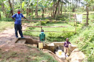 The Water Project: Buhayi Community, Nasichundukha Spring -  Joseph At The Spring With His Two Boys Getting Water For The Cows