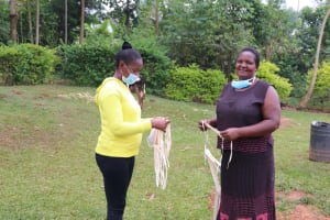 The Water Project: Shitaho Community B, Isaac Spring -  Rosemary Receiving A Mask From Field Officer Christine At Training