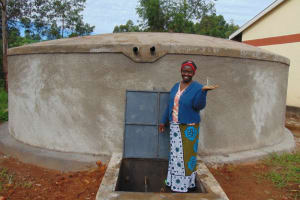 The Water Project: Kapkoi Primary School -  School Staff Holds Cup Of Clean Water From Tank