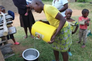 The Water Project: Nguvuli Community, Busuku Spring -  Pouring Water Into Pot For Storage