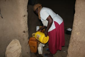 The Water Project: Nguvuli Community, Busuku Spring -  Pouring Water Into Storage Containers