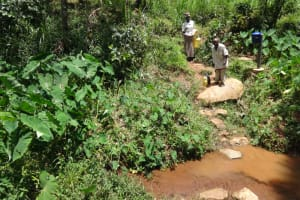 The Water Project: Shihome Community, Peter Majoni Spring -  Assisting An Old Man Fetch Water