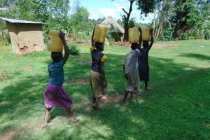 The Water Project: Indulusia Community, Yakobo Spring -  Carrying Water From The Spring