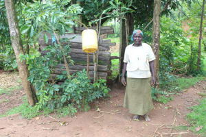 The Water Project: Makale Community, Luyingo Spring -  A Woman Shows Her Bathing Shelter With A Handwashing Point