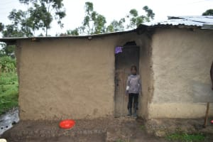 The Water Project: Silungai B Community, Tali Saya Spring -  A Child Ducks Under The Roof As It Rains