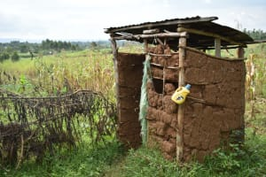 The Water Project: Mukhungula Community, Mulongo Spring -  Latrine With Leaky Tin For Handwashing Tied To Pole