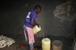 The Water Project: Mukhungula Community, Mulongo Spring -  Nelly Pours Water In Storage Containers At Home