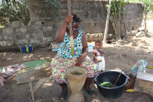 The Water Project: Lungi, Suctarr, #47 Kamara Street -  Woman Pounding Cassava Leaves