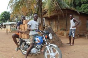 The Water Project: Lokomasama, Rotain Village -  Young Men Transporting Mud Blocks On Motorbike