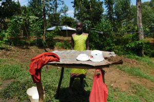 The Water Project: Khaunga A Community, Murutu Spring -  A Girls Stands Next To A Dishrack