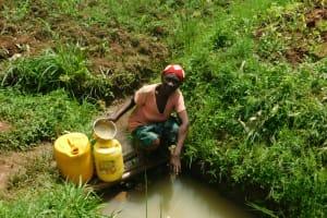 The Water Project: Musango Community, Wambani Spring -  Collecting Water From Wambani Spring